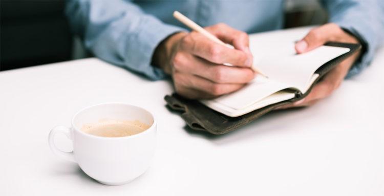 Notizen im Tagebuch am Schreibtisch, Kaffee, Journaling